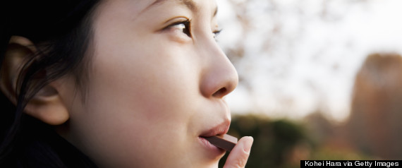 a Japanese girl is eating a piece of chocolate. | location: shinjyuku gyoen, Shinjyuku-ku, Tokyo, Japan